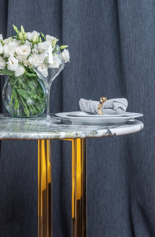 White ceramic plate with crystal wineglass placed on marble table together with bouquet of white flowers in transparent vase