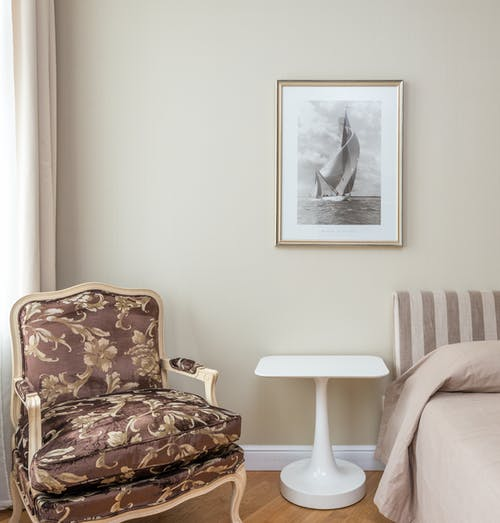 Comfortable armchair with classic design placed in corner of cozy bedroom near bed