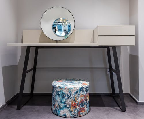 Colorful pouf near table in room