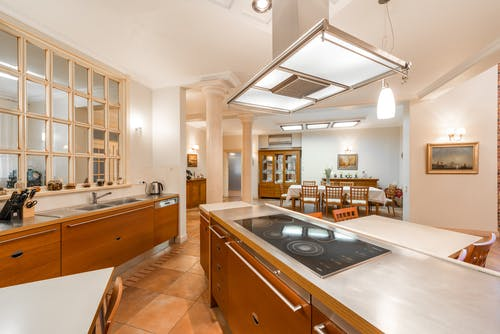 Interior of contemporary spacious kitchen with various appliances and cupboards with dining area