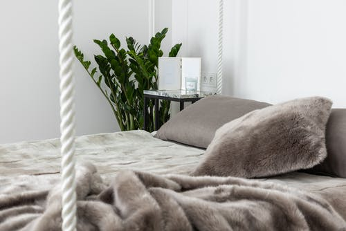 Comfortable bed with pillow and blanket in bedroom