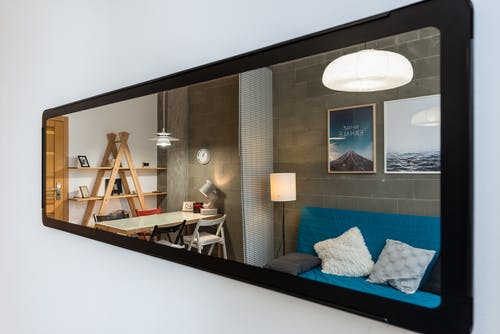 Interior of cozy modern living room with comfortable couch and big table reflected in narrow long mirror