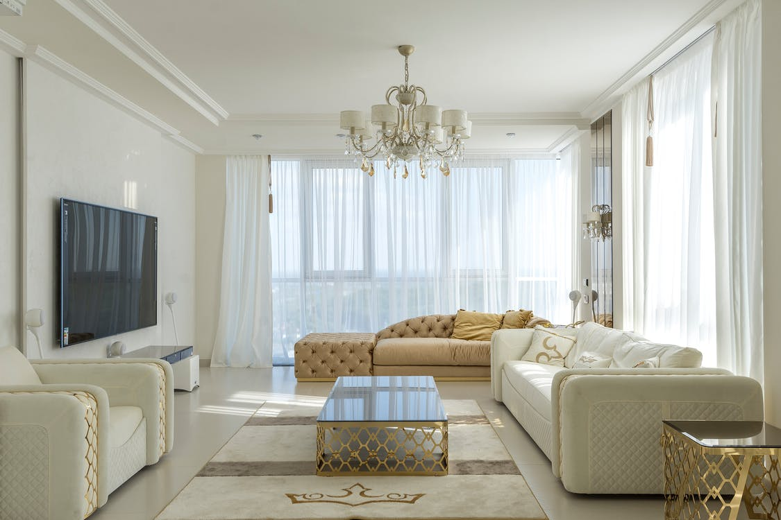Interior of spacious room with huge windows behind curtains and comfortable furniture against TV set