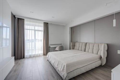 Spacious room with large window behind curtains and double bed against modern TV set
