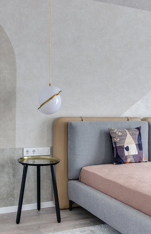 Comfortable bed with colorful pillow near bedside table under lamp with creative design