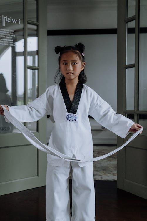 Girl in Karategi Holding a White Belt