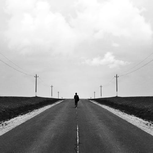 Person Walking on the Road in Grayscale Photography