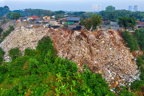 Slope of hill covered with garbage placed near town in daytime