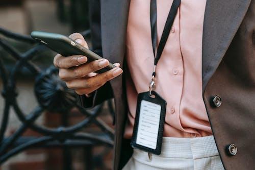 黒のスマートフォンを保持している茶色のボタンアップシャツの人