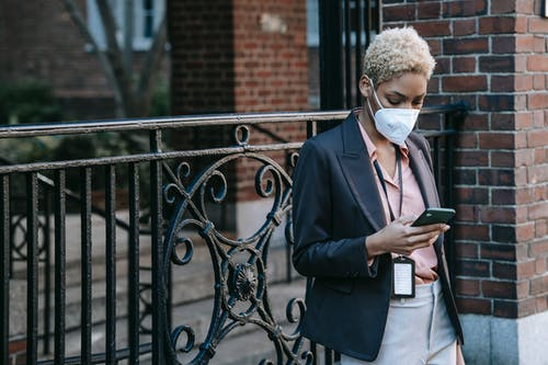 Unrecognizable concentrated young ethnic female entrepreneur with short hair in stylish suit and medical mask messaging on smartphone while standing near brick building on city street