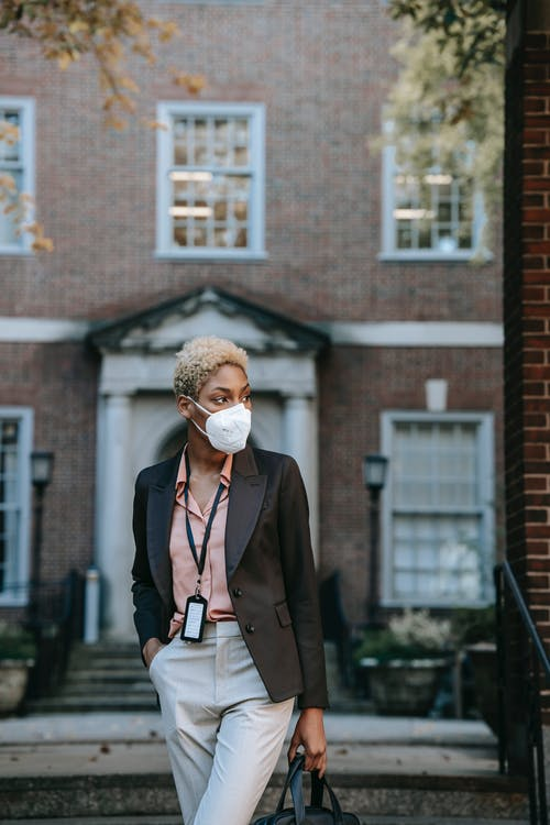 Confident young black lady in medical mask strolling on street