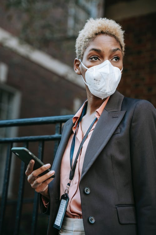 Anonymous focused young African American female manager with short blond hair in formal suit and protective mask using smartphone and looking away while waiting for business meeting on street