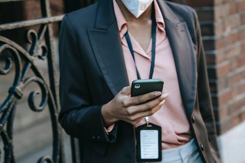 Elegant black female entrepreneur messaging on smartphone on street