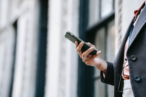 Side view of crop unrecognizable female manager in stylish outfit using mobile phone while standing on street near building before going to work