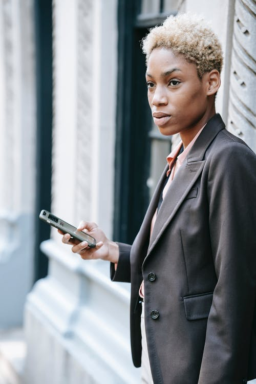 Pensive ethnic female manager messaging on smartphone on street