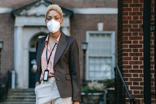 Serious young black female entrepreneur with short dyed hair in stylish suit and protective mask standing on street near brick building with had in pocket and looking at camera
