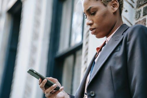 スマートフォンを保持している黒いスーツの女性