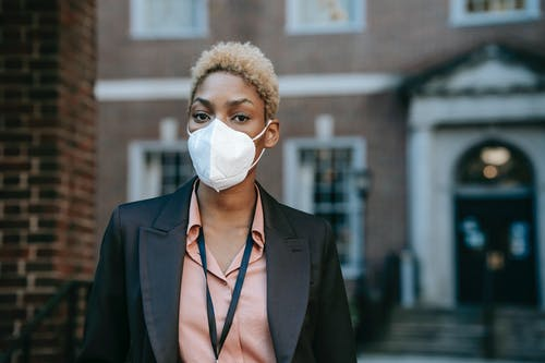 Serious African American female entrepreneur in white protective mask and formal black jacket looking at camera