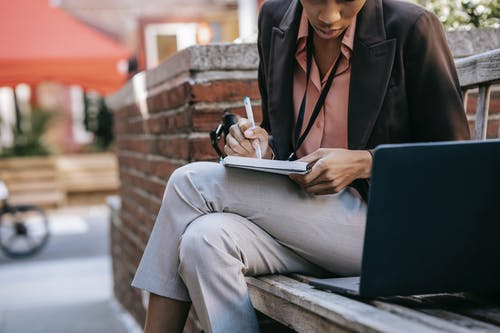 Ethnic woman writing in notebook