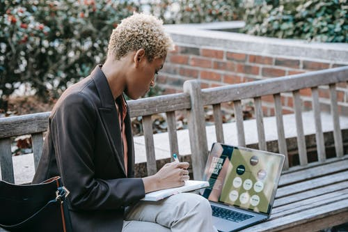 High angle side view of focused African American female employee writing notes while watching presentation on laptop sitting on wooden bench