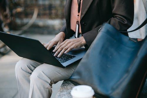 黒のラップトップコンピューターを使用して黒のブレザーと白のズボンの人