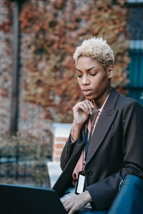 Pensive young African American female freelancer in formal jacket with badge working on laptop touching chin