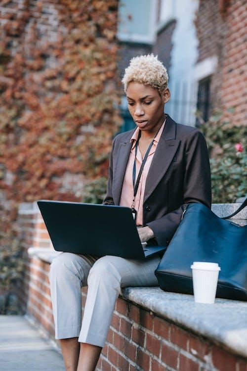 Focused ethnic freelancer with laptop