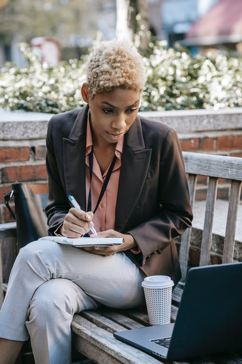 Concentrated young African American businesswoman sitting on wooden bench with legs crossed while taking notes and using laptop
