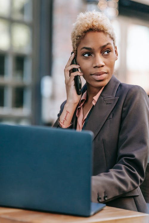 Black woman talking on smartphone and browsing laptop for work
