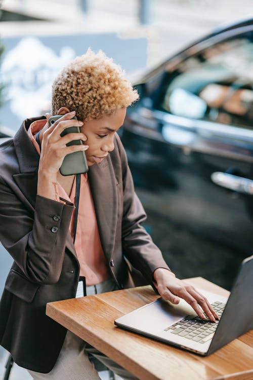 High angle of busy African American female entrepreneur talking on mobile phone and browsing netbook during outdoor remote work