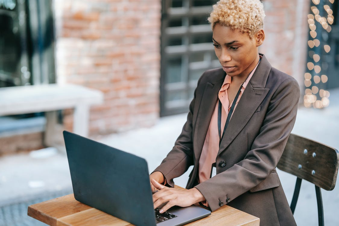 Serious black businessman typing on laptop during remote work