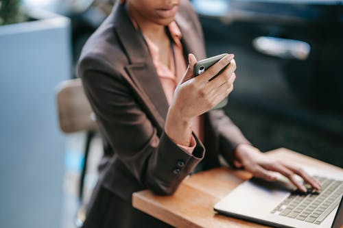 Black woman surfing laptop and using smartphone
