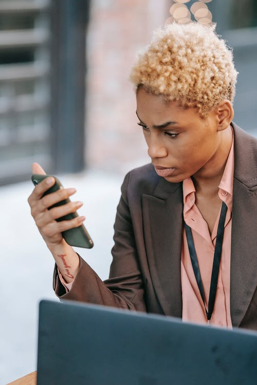 Focused African American female executive watching mobile phone while working on business project remotely