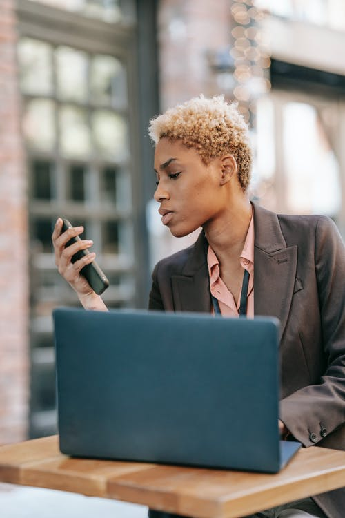 Serious black female entrepreneur watching smartphone and using laptop