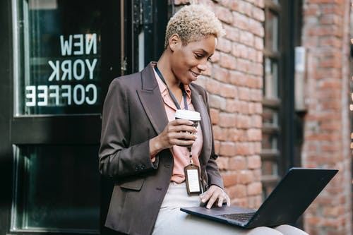 Positive African American businesswoman with cup of coffee browsing netbook in outdoor cafeteria while working remotely