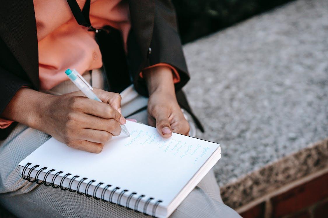 Mujer En Chaqueta Negra Escribiendo En Cuaderno Blanco