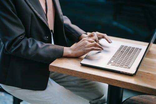 Persona Con Chaqueta De Traje Negro Con Macbook Pro