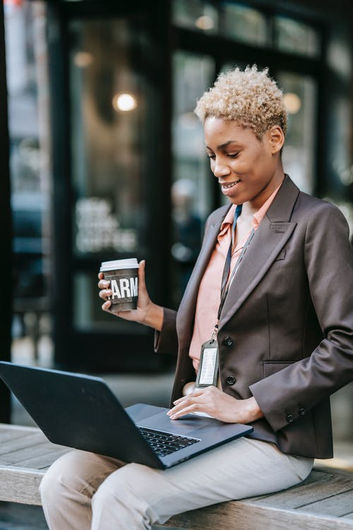 Smiling black businesswoman using laptop and drinking coffee