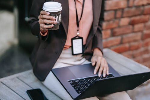 Crop businesswoman with laptop and coffee