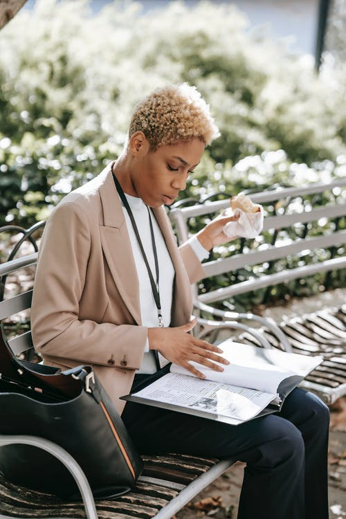 Focused young African American female student sitting on bench in campus and eating sandwich while reading papers