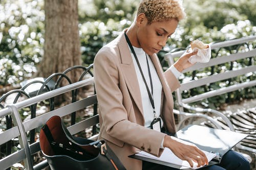 Crop concentrated African American female in classy jacket with badge eating sandwich while reading documents in folder sitting on bench in park