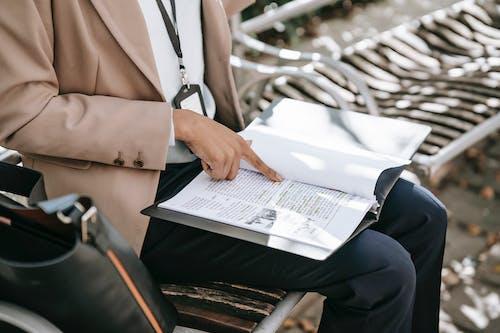 本を読みながら椅子に座っている茶色のブレザーと黒のズボンの人