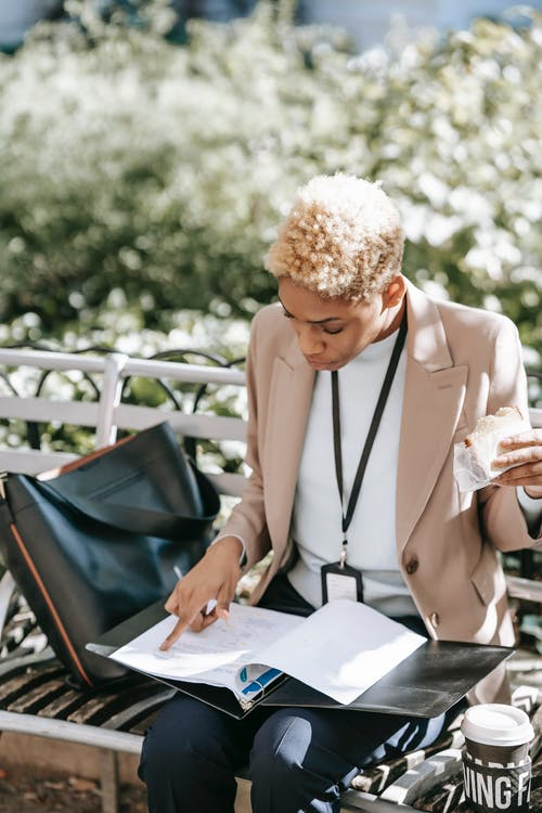 Focused young African American female student with badge eating sandwich on bench in park while looking through papers in folder