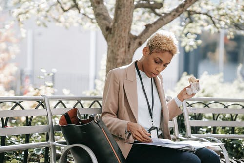Pensive young African American female student in stylish jacket reading documents in folder and eating sandwich sitting in park