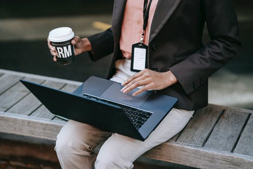 From above of crop anonymous female entrepreneur in stylish black jacket with badge sitting on wooden bench drinking coffee and using laptop