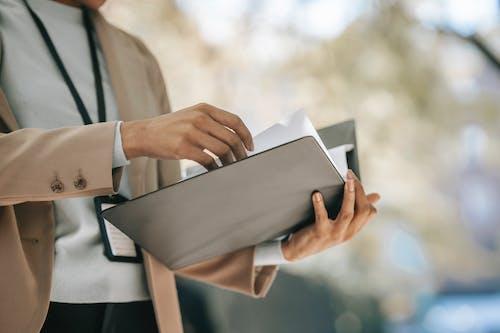 Crop anonymous female entrepreneur in elegant jacket with badge looking through papers in folder