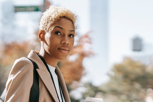 Stylish young African American female in classy jacket drinking coffee while walking in park and looking away