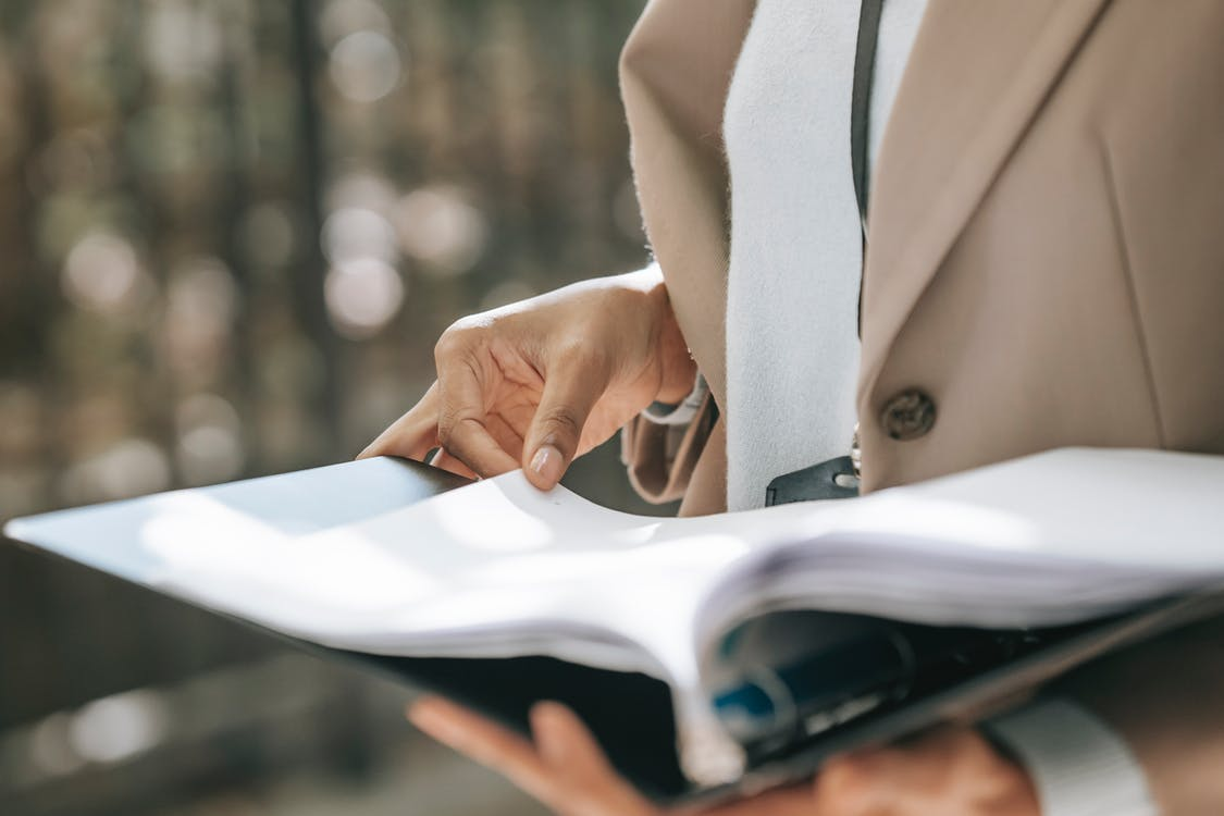 Crop faceless female entrepreneur in stylish jacket reading important documents in black folder