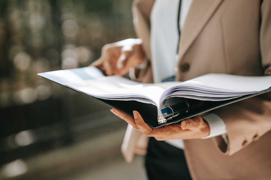 Crop faceless female entrepreneur in formal jacket turning pages of documents in folder while reading