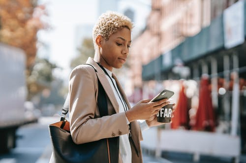 Side view of concentrated young African American female text messaging on smartphone while crossing road and drinking coffee